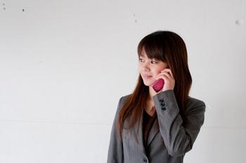 電話で質問している女性