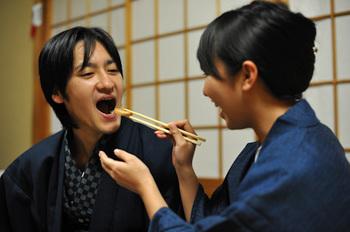旅館で仲良くご飯を食べている恋人たち
